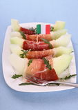 成熟瓜切片用火腿、巴马干酪和意大利旗子 免版税库存图片