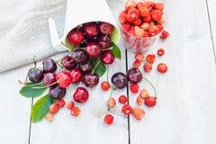 成熟甜樱桃和野草莓在一个圈子在白色木背景 免版税库存图片