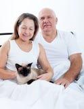 成熟男人和妇女在床上 免版税图库摄影