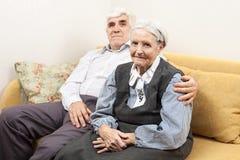 成熟男人和资深妇女坐沙发 库存照片