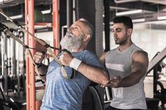 成熟男性有与教练员的锻炼在现代健身房 库存图片
