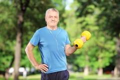 成熟男性行使与重量在公园 免版税库存图片