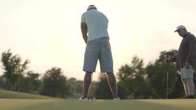 成熟白种人打在高尔夫球领域的人和年轻中东人高尔夫球 击中球的被集中的人 股票录像