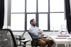 成熟的商业人坐与被交叉的双臂的一把椅子 图库摄影