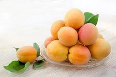 成熟的杏子 与叶子,在一块玻璃板的被折叠的幻灯片的新鲜的杏子 木背景 侧视图 苹果庭院地面收获成熟时间结构树 免版税库存图片