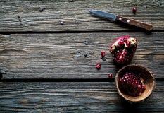成熟石榴、餐巾和餐刀在木背景 免版税库存照片