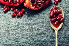 成熟石榴片断和五谷  能胆固醇接近的更低的宏指令一石榴种子射击superfoods 一部分的在花岗岩板和古董匙子的石榴果子 免版税库存照片