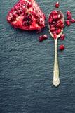 成熟石榴片断和五谷  能胆固醇接近的更低的宏指令一石榴种子射击superfoods 一部分的在花岗岩板和古董匙子的石榴果子 免版税库存图片