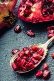 成熟石榴片断和五谷  能胆固醇接近的更低的宏指令一石榴种子射击superfoods 一部分的在花岗岩板和古董匙子的石榴果子 库存照片