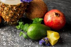 成熟石榴石、明亮的鲕梨、椰子、菠萝和阳桃 椰树芯片、花和薄荷叶在灰色背景 库存图片
