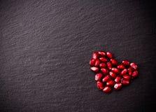 成熟石榴种子以心脏的形式在黑板岩背景的 免版税库存图片