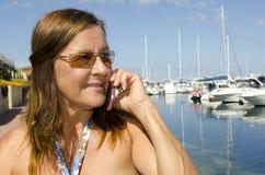 成熟移动电话联系的妇女 免版税库存照片