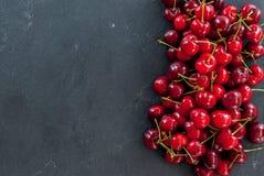 成熟红元帅樱桃堆在黑色的与拷贝空间 免版税库存图片