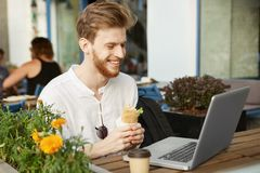 成熟红发人画象有胡子的在休息从工作的偶然白色衬衣,吃午餐的三明治和 免版税库存照片