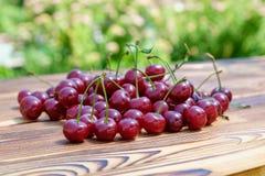 成熟红色樱桃堆在木桌上的 图库摄影
