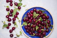 成熟红色樱桃顶视图在蓝色板材和在桌上 免版税库存图片