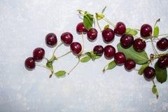 成熟红色樱桃,关闭顶视图在浅灰色的背景的 库存图片