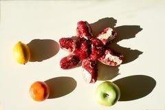 成熟红色水多的石榴,绿色苹果,黄色柠檬,分开橙色普通话谎言在白色背景 免版税库存照片