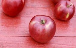 成熟红色苹果在五颜六色的槭树的一张木桌上说谎留下i 免版税库存图片