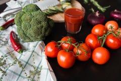 成熟红色蕃茄在一张黑时髦的桌上说谎 在背景中我们看见一杯西红柿汁,红洋葱 库存图片