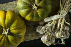成熟美丽的南瓜和大蒜在一个木板 秋天 菜 收获 图库摄影