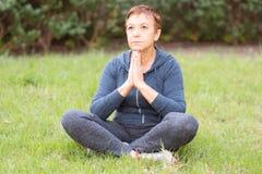 成熟美丽的活跃愉快的妇女早晨在公园,在体育锻炼以后放松 瑜伽姿势的中间夫人 免版税库存照片
