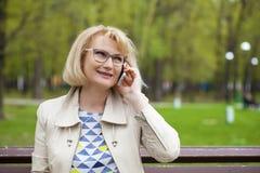 成熟美丽的白肤金发的妇女拜访手机 库存图片