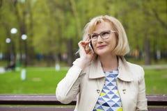 成熟美丽的白肤金发的妇女拜访手机 免版税库存照片