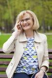 成熟美丽的白肤金发的妇女拜访手机 免版税库存图片