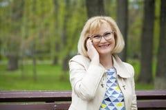 成熟美丽的白肤金发的妇女拜访手机 免版税图库摄影