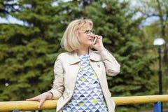 成熟美丽的白肤金发的妇女拜访手机 库存照片