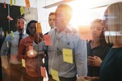 成熟群策群力与稠粘的n一起的经理和他的队 免版税库存图片