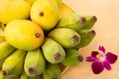 成熟芒果和未加工的香蕉在木表上与兰花花 库存图片