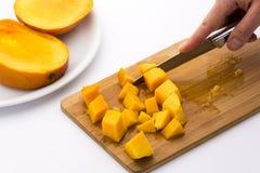 成熟芒果果子黏浆状物质切成小方块与厨刀 免版税库存图片