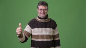 成熟英俊的人佩带的高领衫毛线衣反对绿色背景 影视素材