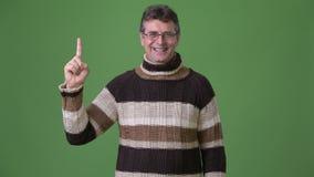 成熟英俊的人佩带的高领衫毛线衣反对绿色背景 股票视频