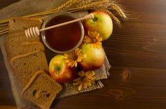 成熟苹果、一个瓶子蜂蜜,黑麦面包、耳朵和黄色雏菊在麻袋布 免版税库存图片