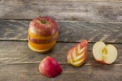 成熟苹果和桔子的混合在一张木书桌上 免版税图库摄影