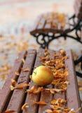 成熟苹果和秋叶在木长凳 免版税图库摄影
