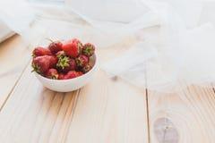 成熟草莓板材在木背景的 库存图片