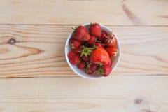 成熟草莓板材在木背景的 免版税图库摄影
