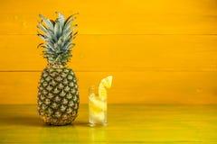 成熟菠萝和汁液在一块玻璃在一黄色木backgroun 库存图片