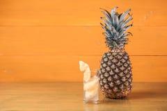 成熟菠萝和汁液在一块玻璃在一黄色木backgroun 免版税库存照片