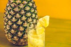 成熟菠萝和汁液在一块玻璃在一黄色木backgroun 免版税图库摄影
