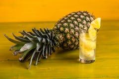 成熟菠萝和汁液在一块玻璃在一黄色木backgroun 免版税库存图片