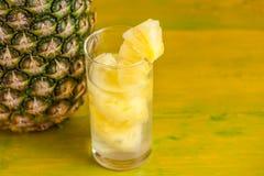 成熟菠萝和汁液在一块玻璃在一黄色木backgroun 库存照片