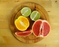 成熟葡萄柚、石灰和桔子在木背景 库存图片