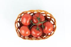 成熟蕃茄分支在一个柳条筐的 查出在白色 免版税库存图片