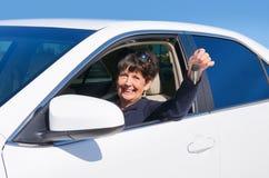 成熟资深妇女司机微笑的w新的汽车钥匙 图库摄影