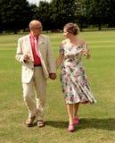 成熟走在草的新娘和新郎 图库摄影
